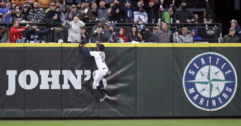Seattle Mariners center fielder Mallex Smith and fans watch the home run ball of Houston Astros' Jose Altuve in the fifth inning of a baseball game Saturday, April 13, 2019, in Seattle. (Elaine Thompson / The Associated Press)