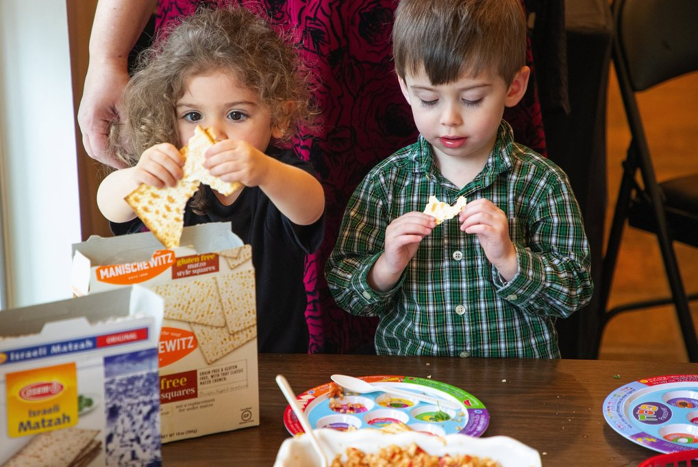 Preschoolers Sora Lefever, left, and Xavier Bardacke try a taste of matzo, or unleavened bread. The food is a key part of the story of Passover. Jews learn that during their escape from Egypt in ancient times, their bread did not have time to rise as they rushed to freedom. During the holiday, Jews commemorate their liberation from slavery by eating matzo instead of bread. (Mike Siegel / The Seattle Times)