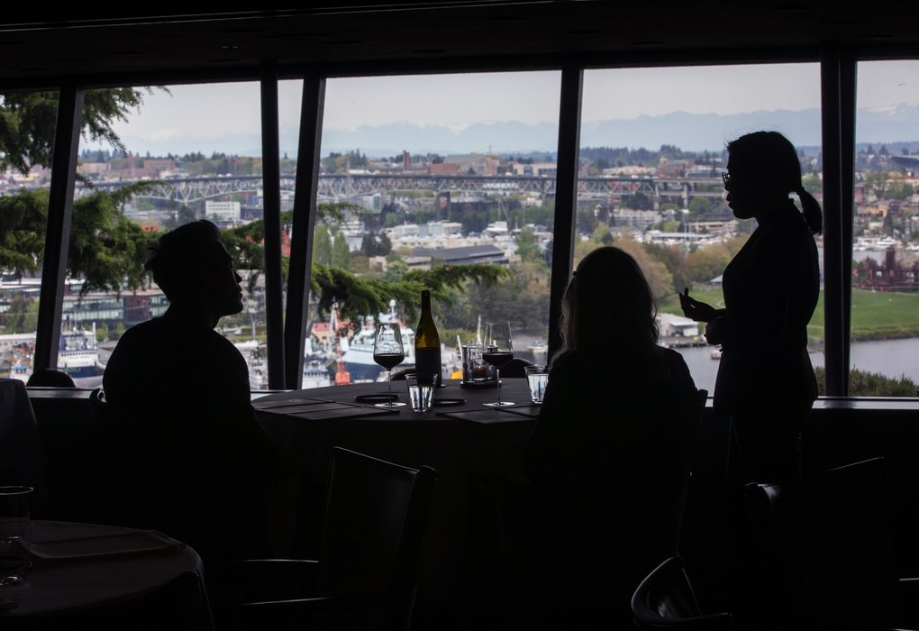 A server waits on guests in front of Canlis' expansive view. (Ellen M. Banner / The Seattle Times)