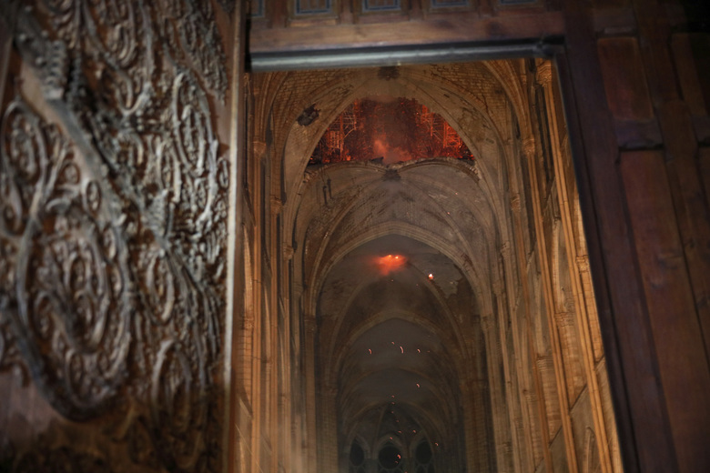 """Smoke, flames, and burning debris inside the Cathedral of Notre-Dame in Paris, Monday night, April 15, 2019. The cathedral remains structurally sound after a monstrous fire roared through it Monday night. But the conflagration that destroyed the wood-and-lead roof and lacy spire also left three """"holes"""" in the sweeping vaulted ceiling, officials said after an inspection on Tuesday. (Philippe Wojazer/Pool via The New York Times) — FOR EDITORIAL USE ONLY. —"""