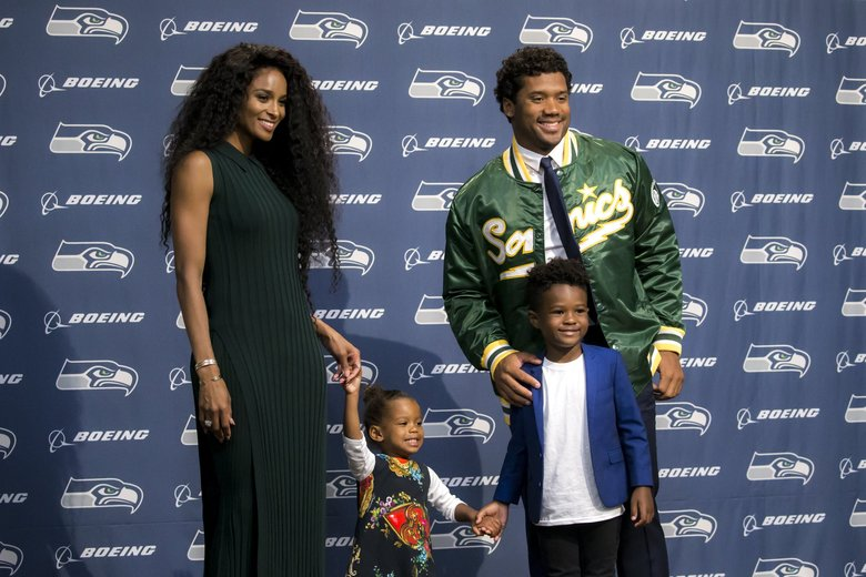 Seahawks quarterback Russell Wilson donned a Sonics jacket for a family photo with his wife Ciara, daughter Sienna Princess Wilson and stepson Future Zahir Wilburn on Wednesday. Earlier this week, Wilson and the Seahawks agreed to a four-year, $140 million contract extension and $65 million signing bonus. The deal keeps him with the Seahawks through the 2023 season and makes him the highest-paid player in the history of the NFL. (Bettina Hansen / The Seattle Times)