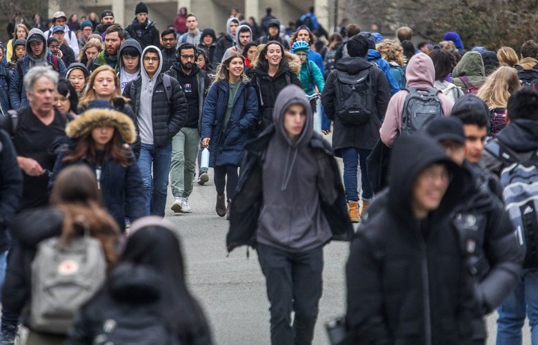 Students walk on the University of Washington campus. A new bill in the Legislature would tax businesses to boost funds for higher education in the state. (Steve Ringman / The Seattle Times)