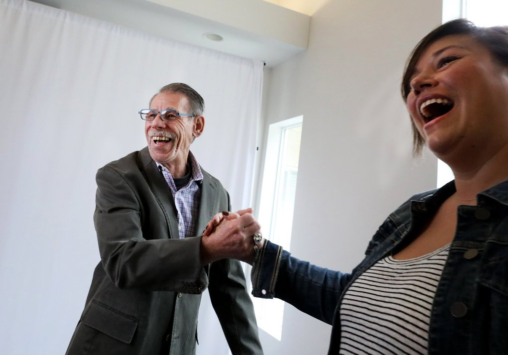 James Rogers gets a congratulatory hand clasp from photographer Sasha Reiko, who documented his makeover in a studio setup she made at the Union Gospel Mission's Burien facility. (Alan Berner / The Seattle Times)
