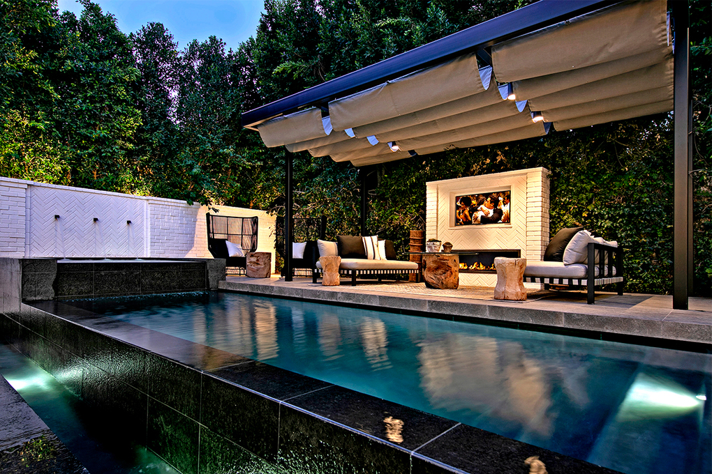 The zero-edge swimming pool (far left) sits next to a cabana with a fire pit and television. (Jim Bartsch via TNS)