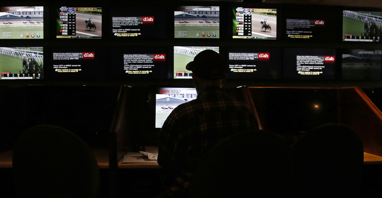 FILE- In this May 21, 2018, file photo, a man watches the off-track betting screens at Riverwind Casino in Norman, Okla. In some states where tribal gambling is prevalent, sports betting bills have not been introduced at all. That's the case in Oklahoma, as well as California and Florida, which are home to politically influential tribes that have been cool to the idea. (AP Photo/Sue Ogrocki, File)