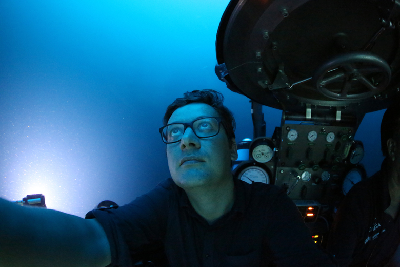 Associated Press reporter, David Keyton, looks out of a submersible at around 400 feet below the surface off the coast of the island of St. Joseph in the Seychelles, Monday April 8, 2019. Able to operate down to 1,000 feet, these manned submersibles give scientists a unique understanding of changes in habitats as sunlight diminishes through the different layers of ocean. (AP Photo/David Keyton)
