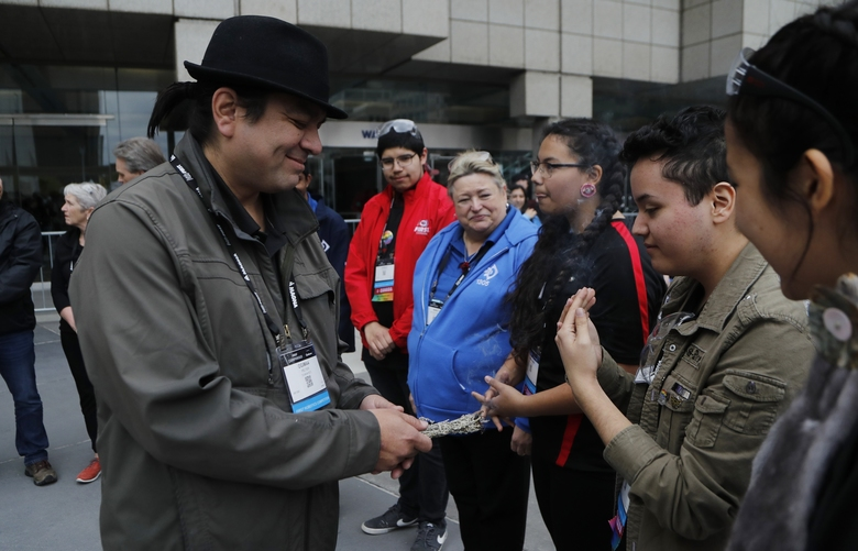 David Jackson, right, takes in the smoke from the burning sage held by First Nation Chief Duke Peltier during a cleansing ceremony outside the First Championship robotics competition, Friday, April 26, 2019, in Detroit. The First Nations STEM team that qualified for its first FIRST Championship is Ontario-based and is the only team made up of all indigenous students. (AP Photo/Carlos Osorio)
