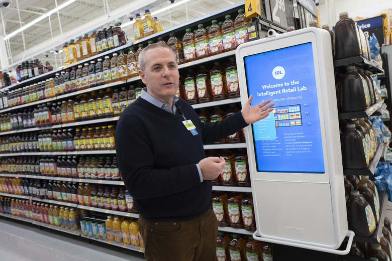 """Mike Hanrahan, CEO of Walmart's Intelligent Retail Lab, discusses a kiosk that describes to customers the high technology in use at a Walmart Neighborhood Market, Wednesday, April 24, 2019, in Levittown, N.Y. """"If we know in real time everything that's happening in the store from an inventory and in stock perspective, that really helps us rethink about how we can potentially manage the store,"""" said Hanrahan. (AP Photo/Mark Lennihan)"""