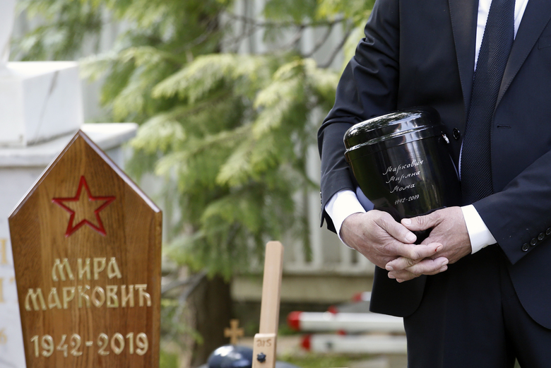 A family friend Slobodan Bulatovic holds urn with ashes of Mirjana Markovic, the widow of former strongman Slobodan Milosevic during her funeral at the yard of his estate in his home town of Pozarevac, Serbia, Saturday, April 20, 2019. Markovic died last week in Russia where she had been granted asylum. The ex-Serbian first lady had fled there in 2003 after Milosevic was ousted from power in a popular revolt and handed over to the tribunal in The Hague, Netherlands. (AP Photo/Darko Vojinovic)
