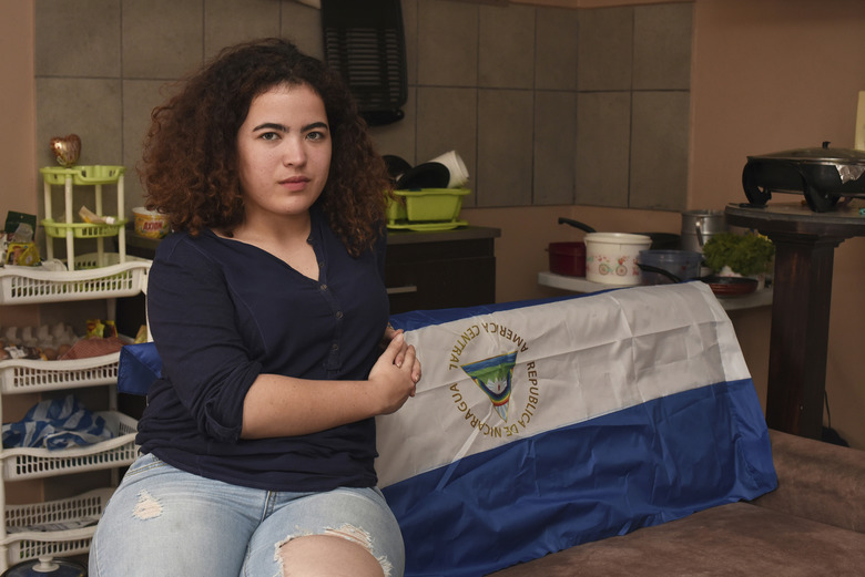 In this March 23, 2019 photo Nicaraguan exile Sadie Rivas, who was active in the protests to oust Daniel Ortega, poses for a photo in her home in San Jose, Costa Rica. She slipped across the border in August after being accused of a laundry list of crimes more associated with a narco-kingpin than a 19-year-old college student: torture, terrorism, money laundering, drug trafficking, weapons possession, destruction of public property, disturbing the peace. Such accusations are typical in cases against protesters, and both they and international observers call them groundless. (AP Photo/Carlos Gonzalez)