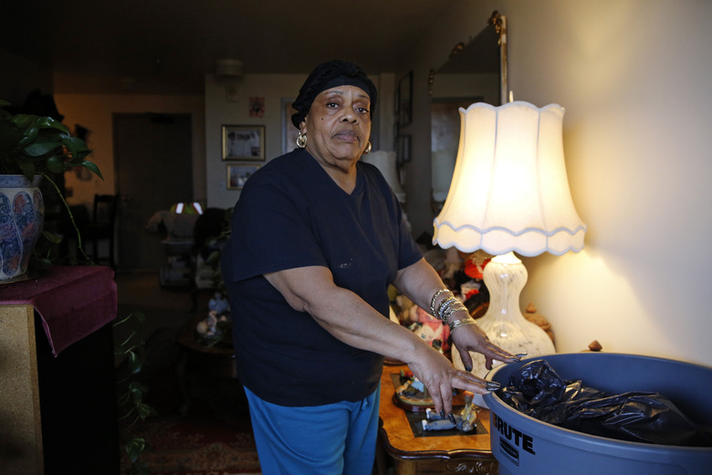 In this Feb. 26, 2019 photo, Della Thomas stands with a trash can that she says management provided to catch water dripping from her ceiling during rain storms in her Rosemont Tower apartment in Baltimore. Largely due to complexes such as Rosemont Tower, since 2013 Maryland had the country's highest inspection failure rate for public housing at 32%. (AP Photo/Patrick Semansky)