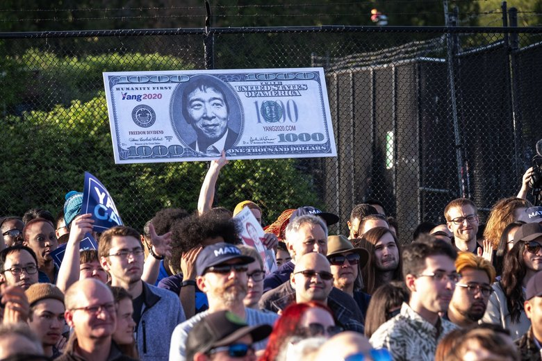 A supporter of Andrew Yang holds up a giant sign with the tech entrepreneur's face at Friday's rally. (Dean Rutz / The Seattle Times)