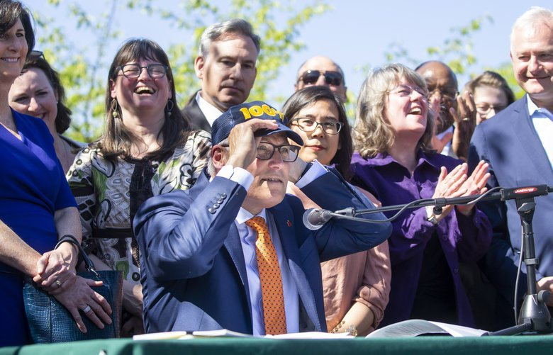 Governor Jay Inslee puts on a symbolic 100% hat before signing Senate Bill 5116 into law in front of a crowd in the Rainier Vista development in the Columbia City neighborhood of Seattle Tuesday May 7, 2019. The bill is one of five Inslee signed on Tuesday aimed at addressing climate change. It requires Washington State utility companies to transition to carbon-neutral supplies for electricity in 2030, and would eliminate fossil fuels from power generation by 2045. It makes Washington the fourth state to legislate the transition to 100% clean electricity. 210176