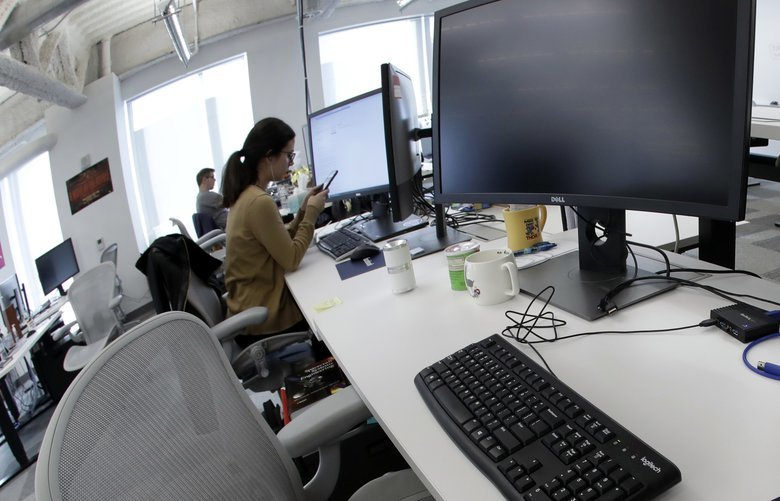 FILE- In this Jan. 9, 2019, file photo, Facebook employees sit at their stations during a tour of its new 130,000-square-foot offices in Cambridge, Mass. Facebook is raising what it pays U.S. contractors who do some of its most taxing work, including watching violent and other objectionable material for possible removal from the service. Facebook said Monday, May 13, that it will pay at least $18 an hour for these jobs. (AP Photo/Elise Amendola, File) NYBZ160 NYBZ160