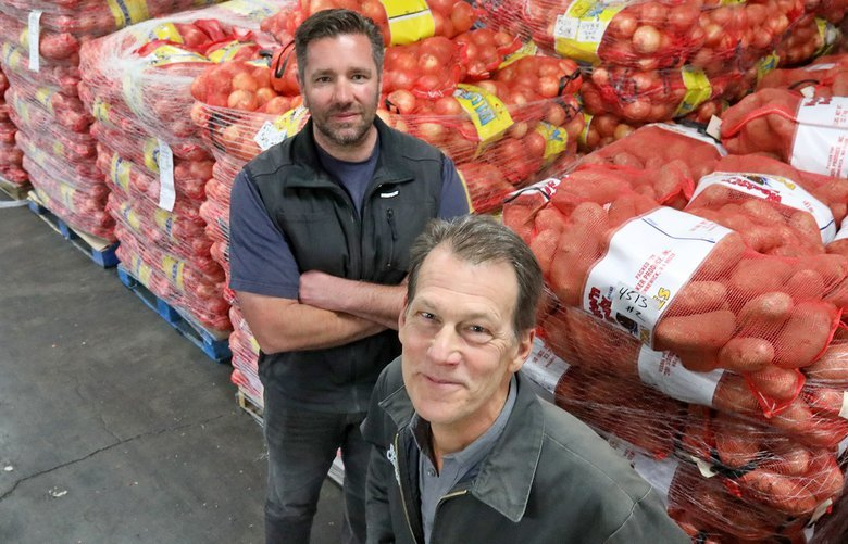 At F.C Bloxom Produce Company, Brian Bernard, left, is export manager and Bill Bloxom, right, is 3rd generation family owner. They're in their SoDo warehouse, with onions and potatoes in the background.  Paul Roberts story for business page 210297