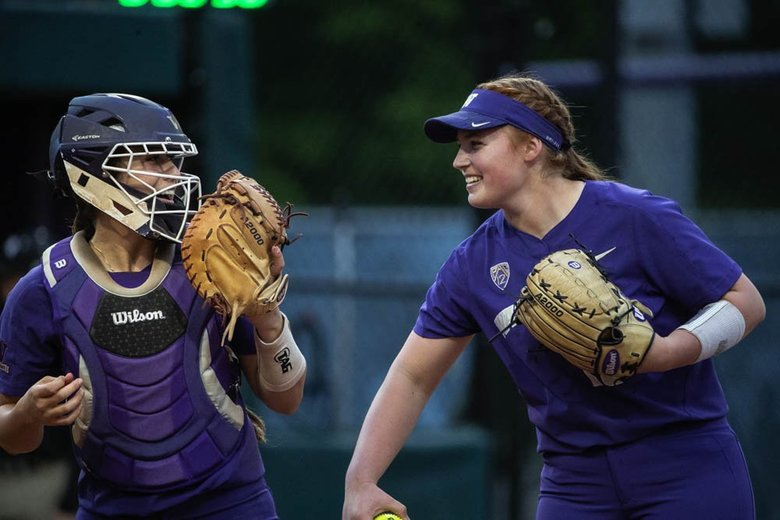 Pitcher Gabbie Plain and catcher Morganna Flores talk in the circle during Sunday's game.  Plain threw her third no-hitter of the season in blanking Mississippi State 8-0 in the NCAA Regionals. (Dean Rutz / The Seattle Times)
