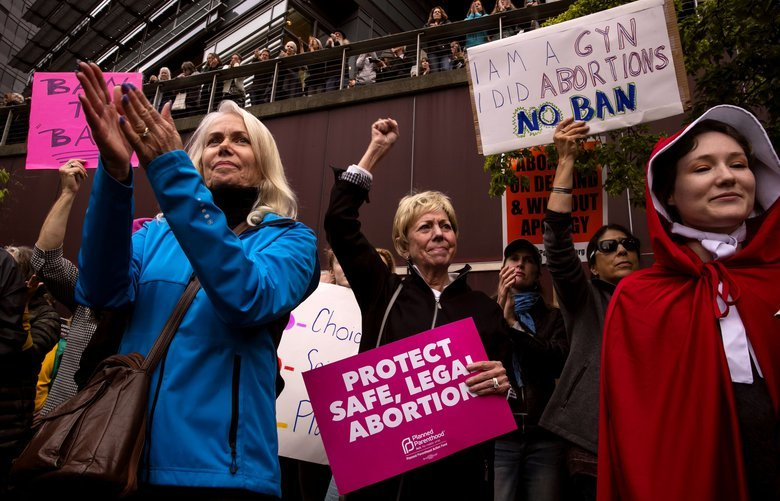 Tanya Guenther, center, holds up her fist during the #StopTheBans rally advocating for reproductive health and rights at Seattle City Hall Tuesday, May 21, 2019. Local politicians and organizations spoke at the event including members of the Seattle City Council, NARAL Pro-Choice Washington, Northwest Abortion Access Fund,  EMILY's List, UltraViolet, Indivisible, All* Above All, MoveOn and others. 210346