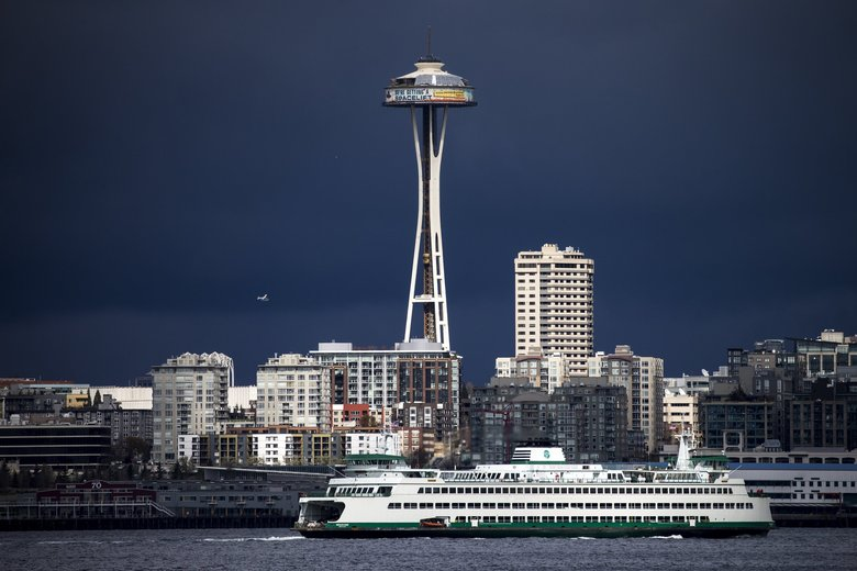 Bright sun lights up the Space Needle as a seaplane and the M/V Wenatchee pass by with dark clouds looming in the background, April 1, 2018.  (Bettina Hansen / The Seattle Times)