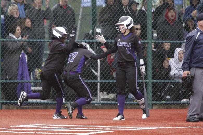 Garfield players Miracle Davis, from left, and Isis Beauregard-Coaxum celebrate with Nicola Simpson after coming home in the fourth inning of a 3A State Final Softball game against Yelm at the Regional Athletic Complex in Lacey, Wash., Saturday May 25, 2019. Garfield defeated Yelm 10-4 to win the state title.   (Jason Redmond / Special to The Seattle Times)