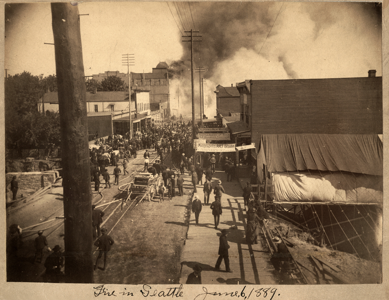 "THEN: Only a handful of images exist of the actual fire — taken by professional photographer William Boyd, whose studio was lost to the flames. Shot from the corner of Spring and Front streets, our ""Then"" photo looks south to smoke billowing up from Madison Street, where the fire began. The grand pioneer landmark Frye's Opera House looms large (upper left), just after catching fire. None of the visible structures survived. (Courtesy Dr. Wayne Pazina)"