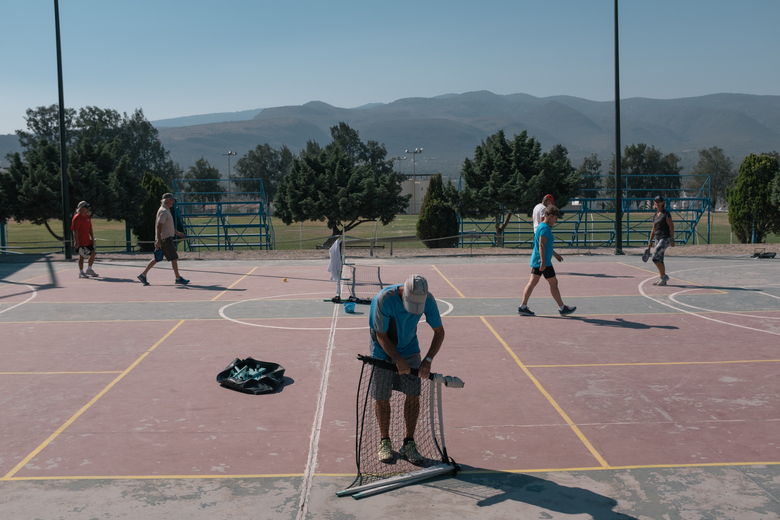 A man folds a pickleball net in San Miguel de Allende, Mexico. American retirees gather at the municipal sports center several days a week to play the sport favored by seniors in the United States. (Photo for The Washington Post by Luis Antonio Rojas).