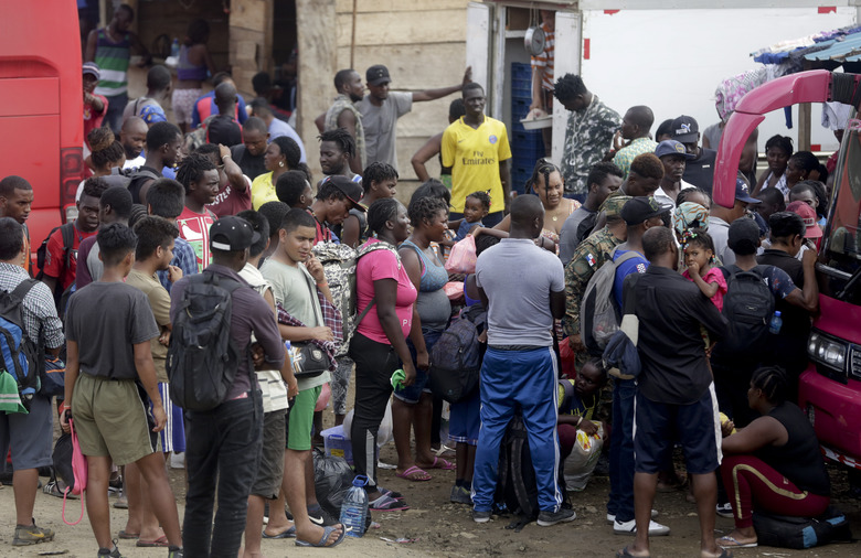 In this May 10, 2019 photo, a group migrants wait for a bus to take them north, in Peñitas, Darien Province, Panama. The U.N. Refugee Agency's Panama office said it visited the camp in early May to counsel migrants about applying for asylum and mechanisms for people in need of international protection. (AP Photo/Arnulfo Franco)