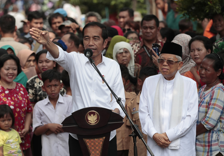 Indonesian President Joko Widodo, left, gestures while his running mate Ma'ruf Amin listens during a speech declaring their victory in the country's presidential election, at a slum in Jakarta, Indonesia, Monday, Tuesday, May 21, 2019. Indonesia's President Joko Widodo has been elected for a second term, official results showed Tuesday, in a victory over a would-be strongman who aligned himself with Islamic hardliners. (AP Photo/Dita Alangkara)