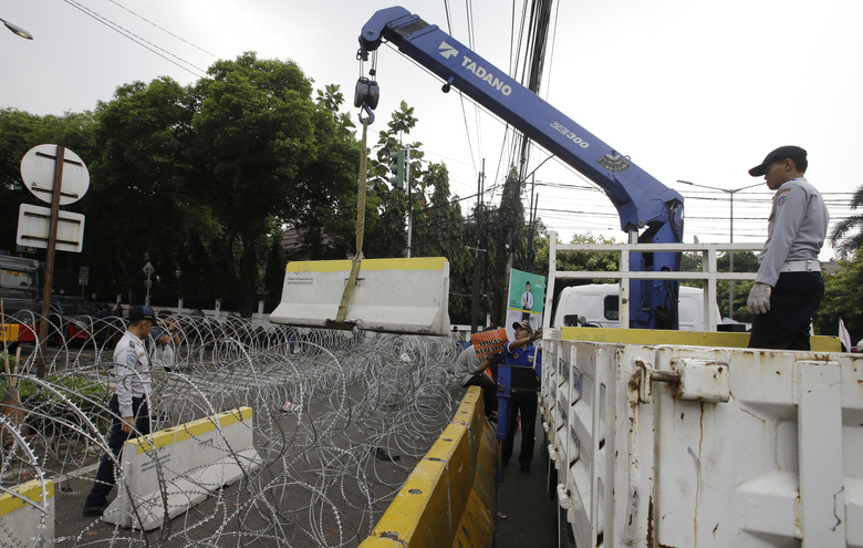 Officials put roadblocks near Election Commission building in Jakarta, Indonesia, Tuesday, May 21, 2019. Indonesia's President Joko Widodo has been elected for a second term, official results showed Tuesday, in a victory over a would-be strongman who aligned himself with Islamic hardliners. Thousands of police and soldiers are on high alert in the capital Jakarta, anticipating protests from Widodo's challenger Prabowo Subianto's supporters. (AP Photo/Achmad Ibrahim)