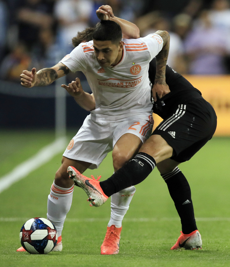 Atlanta United defender Franco Escobar (2) works around Sporting Kansas City forward Krisztian Nemeth during the first half of an MLS soccer match in Kansas City, Kan., Sunday, May 5, 2019. (AP Photo/Orlin Wagner)