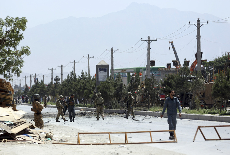 NATO and Afghan forces gather at the site of a suicide car bomb in Kabul, Afghanistan, Friday, May 31, 2019. In a second suicide attack in as many days to rattle the Afghan capital, a car bomb targeting a U.S. convoy exploded early Friday morning in an eastern neighborhood, police said. (AP Photo/Rahmat Gul)