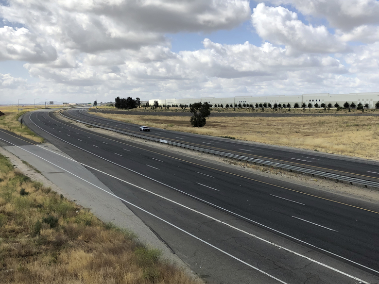 CORRECTS TO PARKED, NOT MOVING – A California Highway Patrol car is parked along an empty Interstate 215 on Friday, May 17, 2019, in California. A wide area including the 215 freeway remained off-limits around an F-16 fighter jet crash site in Southern California on Friday as military and civilian authorities investigated. (AP Photo/Amy Taxin)