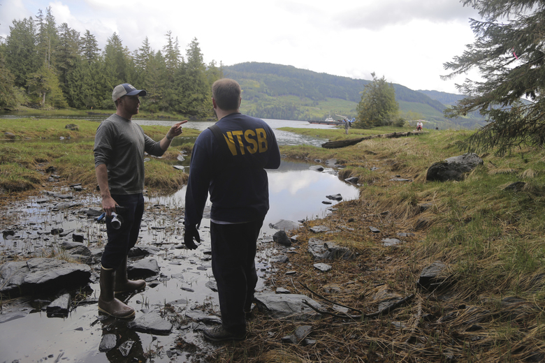 In this photo provided by the National Transportation Safety Board, NTSB investigators Josh Lindberg, left, and Eric Swenson discuss, Wednesday, May 15, 2019, the next steps in the process of documenting and recovering the wreckage associated with the DHC-2 Beaver that was involved in a midair collision near Ketchikan, Alaska, a couple of days earlier. (Peter Knudson/NTSB via AP)