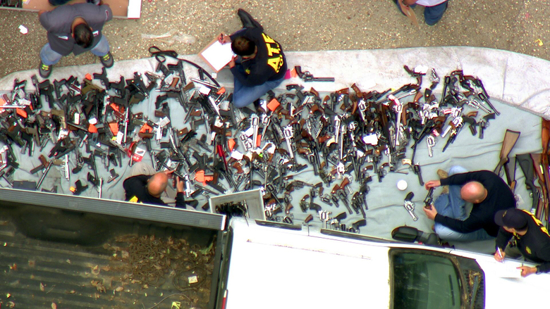 This photo from video provided by KCBS/KCAL-TV shows investigators from the U.S. Bureau of Alcohol, Tobacco, Firearms and Explosives and the police inspecting a large cache of weapons seized at a home in the affluent Holmby Hills area of Los Angeles Wednesday (KCBS/KCAL-TV via AP)