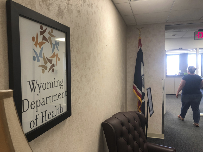 In this photo taken Friday, May 24, 2019, is the entrance to the Wyoming Department of Health headquarters office in Cheyenne, Wyo.  Legal representatives of dozens of Wyoming State Hospital patients say serious problems persist at the state Health Department facility four years after an incapacitated woman was left on a dayroom couch for over 24 hours without food, water or bathroom use. Department officials say major renovations and other improvements will improve conditions. (AP Photo/Mead Gruver)