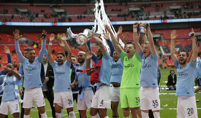 Manchester City's Vincent Kompany lifts the trophy as celebrates with his teammates after winning the English FA Cup Final soccer match between Manchester City and Watford at Wembley stadium in London, Saturday, May 18, 2019. Manchester City won 6-0. (AP Photo/Tim Ireland)