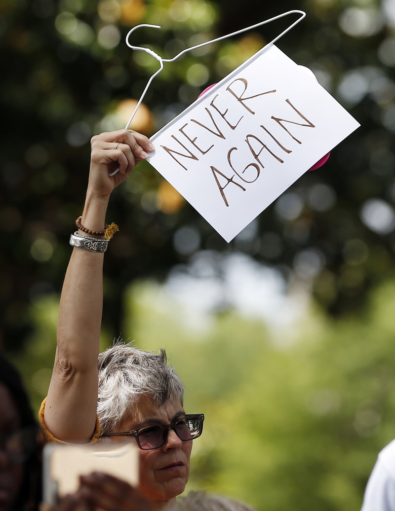 Mindy Brown, of Yazoo City, Miss. holds up a sign and a hanger at the Capitol in Jackson, Miss., voicing her opposition to state legislatures passing abortion bans that prohibit most abortions once a fetal heartbeat can be detected, Tuesday, May 21, 2019. In addition, there are no provisions for rape or incest. Mississippi is among the states that have passed and signed into law such legislation. (AP Photo/Rogelio V. Solis)