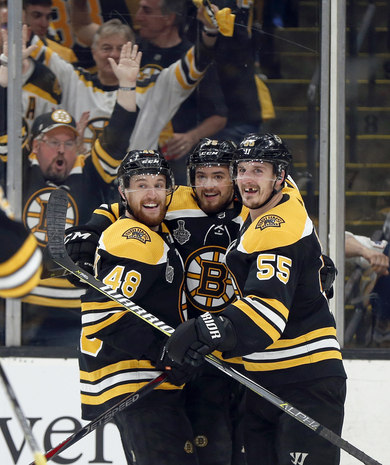 Boston Bruins' Connor Clifton, center, celebrates his goal with Matt Grzelcyk, left, and Noel Acciari, right, during the second period in Game 1 of the NHL hockey Stanley Cup Final against the St. Louis Blues, Monday, May 27, 2019, in Boston. (AP Photo/Michael Dwyer)