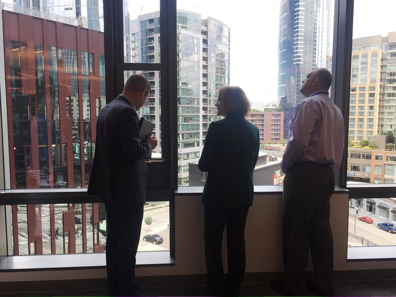 Seattle Mayor Jenny Durkan, center, talks with Amazon vice president of global real estate John Schoettler, left, and Monty Anderson, executive secretary of the Seattle Building and Construction Trades Council, while taking in the view from a lower floor Amazon's newest office tower on Thursday, June 27, 2019.  (Benjamin Romano / The Seattle Times)