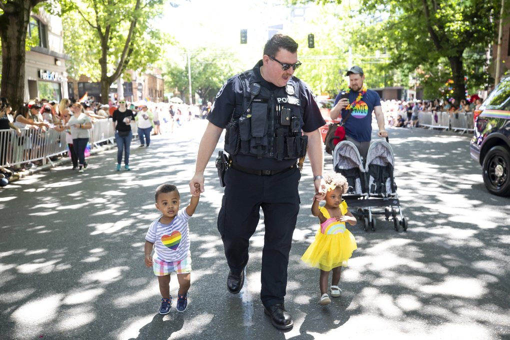 Seattle Police Sgt. Doug Raguso walks his two children in the 45th annual Seattle Pride Parade on Sunday. His husband, Tom Hove, pushes their stroller at right.  (Bettina Hansen / The Seattle Times)