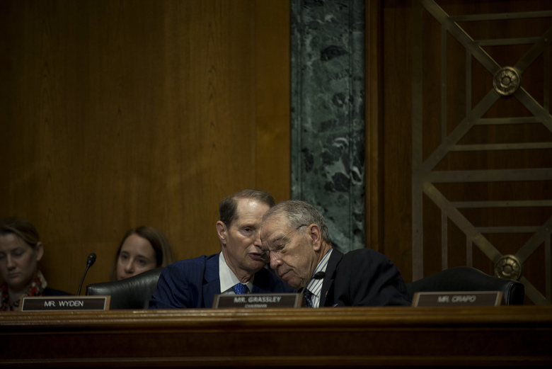 Sen. Ron Wyden (D-Ore.), left, the ranking Democrat, speaks with Senate Finance Committee Chairman Chuck Grassley (R-Iowa) during the Senate Finance Committee hearing to examine President Donald Trump's trade policy agenda on Capitol Hill in Washington, June 18, 2019. (Gabriella Demczuk/The New York Times)