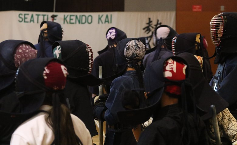 Kendo participants take their places on the gym floor for one-on-one combat at a Seattle Kendo Kai session. (Alan Berner / The Seattle Times)
