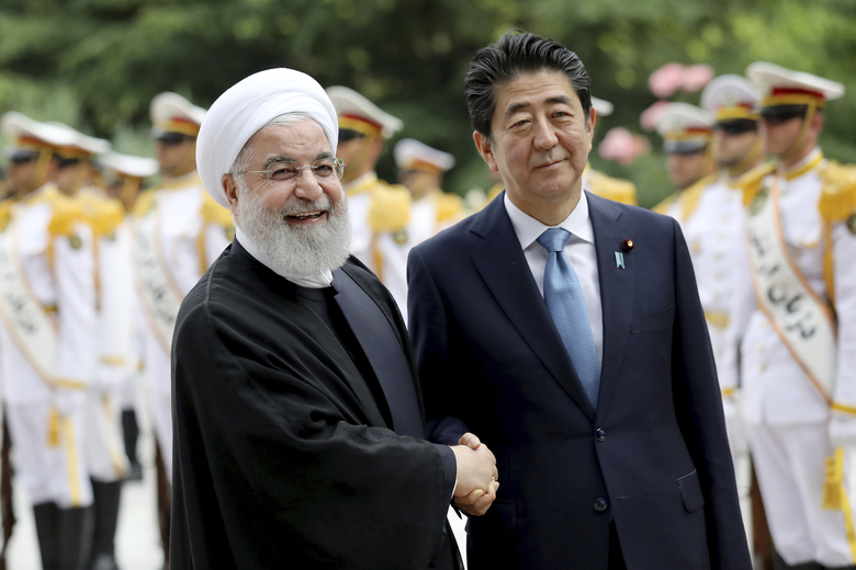 Japanese Prime Minister Shinzo Abe, right, shakes hands for the cameras with Iranian President Hassan Rouhani, during the official arrival ceremony, at the Saadabad Palace in Tehran, Iran, Wednesday, June 12, 2019. (AP Photo/Ebrahim Noroozi)