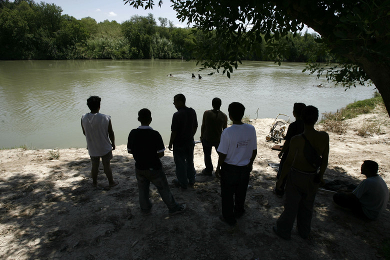 FILE – In this May 25, 2006 file photo, thirty days after crossing into Mexico, Honduran migrants watch from the Mexican side of the Rio Grande as others take a bath as they wait for a good moment to cross the river into the U.S., from the border city of Nuevo Laredo, Mexico. The Mexican border city of Nuevo Laredo is to begin receiving migrants returned from the United States to wait in Mexico while their asylum claims wind their way through U.S. courts, according to Nuevo Laredo Mayor Enrique Rivas on Monday, June 24, 2019. (AP Photo/Dario Lopez-Mills, File)