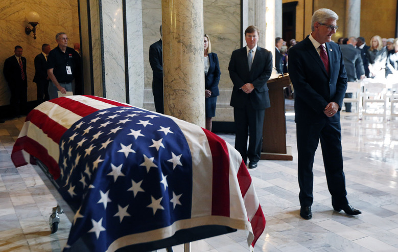 Mississippi Gov. Phil Bryant, right, walks past the casket of the late Republican Sen. Thad Cochran, after paying his respects in the Mississippi State Capitol rotunda in Jackson, Miss., Monday, June 3, 2019. Bryant later spoke during the funeral service, the first of two. Cochran was 81 when he died Thursday in a veterans' nursing home in Oxford, Mississippi.  (AP Photo/Rogelio V. Solis)