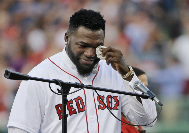 """FILE – In this June 23, 2017, file photo, Boston Red Sox baseball great David Ortiz wipes a tear at Fenway Park in Boston as the team retires his number """"34"""" worn when he led the franchise to three World Series titles. Ortiz was back in Boston for medical care after authorities said the former Red Sox slugger affectionately known as Big Papi was ambushed by a gunman at a bar in his native Dominican Republic. A plane carrying the 43-year-old retired athlete landed Monday night, June 10, 2019, after a flight from the Dominican Republic, the team said.  (AP Photo/Elise Amendola, File)"""