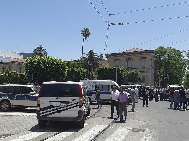 Ambulances and police cars park near an explosion site in Tunis, Thursday June 27, 2019. The Tunisian Interior ministry said one police officer has died in the suicide bombing targeting a police patrol in a busy commercial street in central Tunis. (AP Photo/Riadh Dridi)