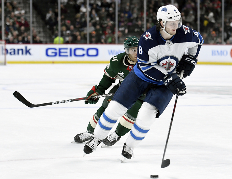 FILE – In this April 2, 2019, file photo, Winnipeg Jets defenseman Jacob Trouba (8) has the puck while shorthanded against Minnesota Wild center Luke Kunin (19) during the second period of an NHL hockey game in St. Paul, Minn. The New York Rangers have acquired Trouba from the Jets for defenseman Neal Pionk and the 20th overall pick in the draft. The teams announced the trade Monday, June 17, 2019. (AP Photo/Hannah Foslien, File)