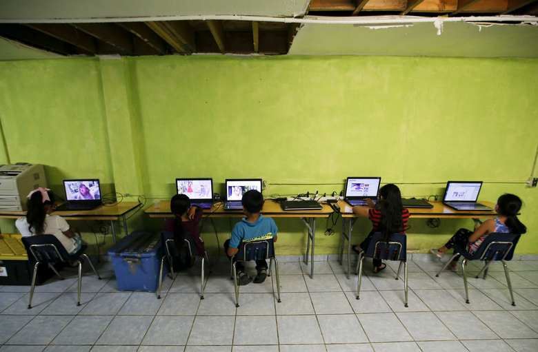 Migrant children watch laptops inside the Agape World Mission shelter used mostly by Mexican and Central American migrants who are applying for asylum in the U.S., on the border in Tijuana, Mexico, Monday, June 10, 2019. (AP Photo/Eduardo Verdugo)