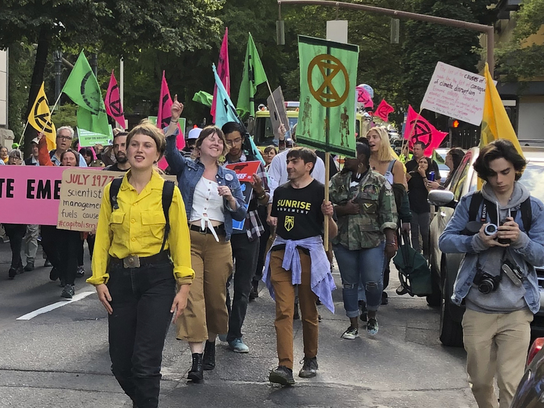 In this photo taken June 21, 2019, people demonstrating to raise awareness of climate change blocked streets in downtown Portland, Ore. The divide in Oregon between the state's liberal, urban population centers and its conservative and economically depressed rural areas makes it fertile ground for the political crisis unfolding over a push by Democrats to enact sweeping climate legislation. Just three years after armed militia members took over a national wildlife refuge in southeastern Oregon, some of the same groups are now seizing on a walkout by Oregon's GOP senators to broadcast their anti-establishment message. (AP Photo/Steven Dubois)