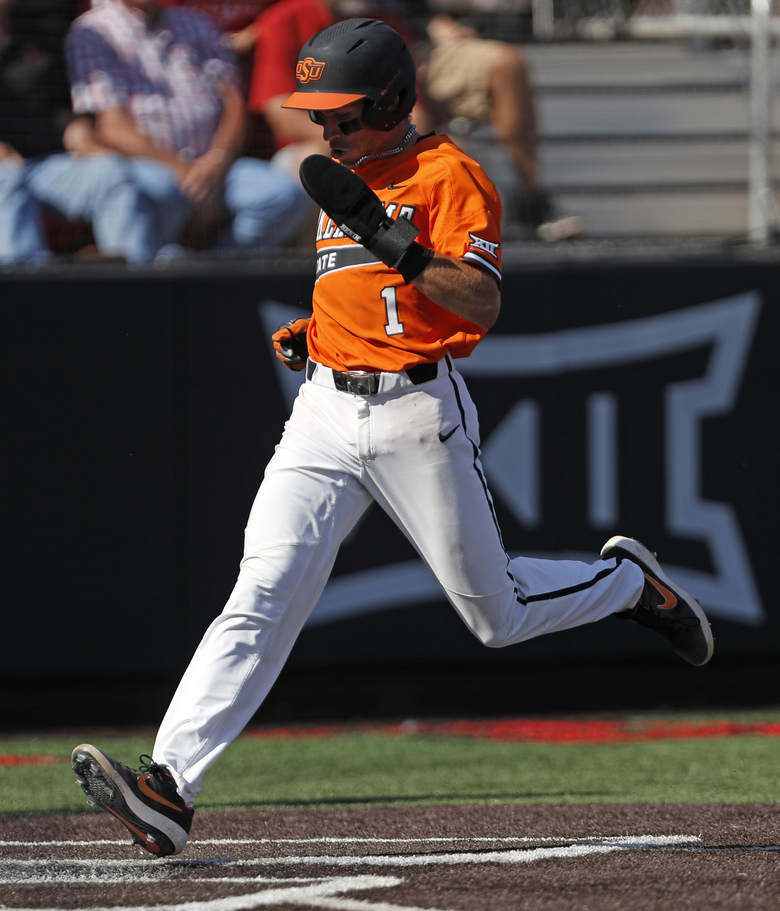 Oklahoma State's Hueston Morrill scores a run during the first inning in Game 2 of the team's NCAA college baseball tournament super regional against Texas Tech, Saturday, June 8, 2019, in Lubbock, Texas. (AP Photo/Brad Tollefson)